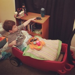 At home, propped up in his wagon so he can play with his cars. More challenging than it looks!